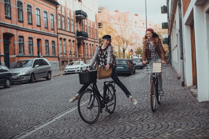 Photo of a young women riding their bikes through city
